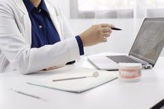Dentista che lavora nell'ufficio del dentista che spiega processo del trattamento alla pazienza, concetto medico di salute immagine stock libera da diritti