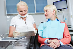 Dentista che legge cartella sanitaria del paziente Fotografie Stock Libere da Diritti