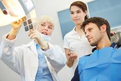 Dentista che mostra la carie sull'immagine dei raggi x Fotografie Stock Libere da Diritti