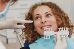 Dentista che paragona la tonalità paziente dei denti del ` s ai campioni per il bleachi fotografie stock