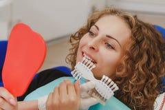 Dentista che paragona la tonalità paziente dei denti del ` s ai campioni per il bleachi fotografia stock
