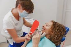 Dentista che paragona la tonalità paziente dei denti del ` s ai campioni per il trattamento di candeggio fotografia stock