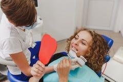Dentista che paragona la tonalità paziente dei denti del ` s ai campioni per il trattamento di candeggio immagine stock