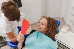 Dentista che paragona la tonalità paziente dei denti del ` s ai campioni per il trattamento di candeggio immagini stock libere da diritti