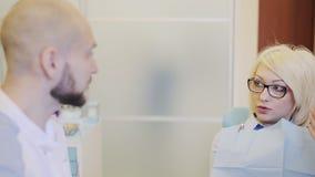 Dentista che parla con paziente archivi video