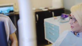 Dentista che parla con paziente stock footage