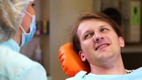 Dentista che parla con paziente dell'uomo dopo l'esame video d archivio