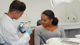 Dentista che parla con suo paziente che mostra la sua muffa dentaria immagini stock