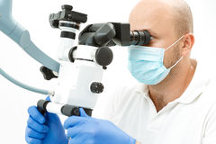 Dentista che per mezzo del microscopio dentario durante l'ispezione Immagini Stock Libere da Diritti