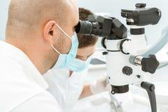 Dentista che per mezzo del microscopio dentario durante l'ispezione Fotografia Stock