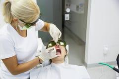 Dentista che per mezzo di un laser dentario del diodo moderno Fotografie Stock Libere da Diritti