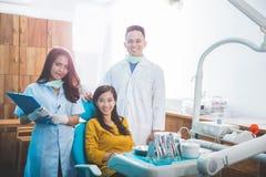 Dentista che sorride con il paziente femminile in clinica dentaria Immagine Stock Libera da Diritti