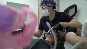 Dentista che tratta i denti al paziente della donna in clinica Stomatologo professionale femminile di medico sul lavoro Assegno d stock footage