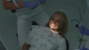 Dentista che tratta i denti pazienti biondi femminili con l'aiuto della macchina della sbavatura Primo piano stock footage