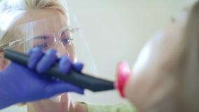 Dentista che usando luce di trattamento dentaria per la cavità orale Riempimento professionale dei denti stock footage