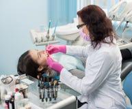 Dentista com ferramentas dentais - espelhe e sonde a verificação acima dos dentes pacientes no escritório dental da clínica Medic imagem de stock