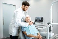 Dentista com a mulher mais idosa antes do procedimento no escritório dental foto de stock