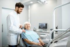 Dentista com a mulher mais idosa antes do procedimento no escritório dental foto de stock royalty free