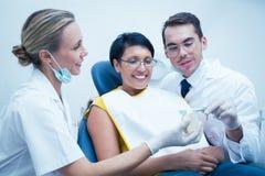 Dentista com a mulher mostrando assistente como escovar os dentes foto de stock