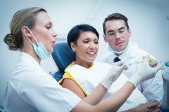 Dentista com a mulher mostrando assistente como escovar os dentes imagem de stock royalty free