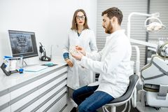 Dentista com o assistente no escritório dental imagem de stock royalty free