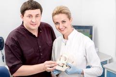 Dentista com o assistente no escritório dental imagem de stock