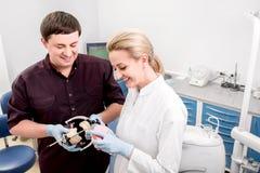 Dentista com o assistente no escritório dental imagens de stock