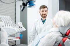 Dentista com o paciente superior da mulher no escritório dental foto de stock
