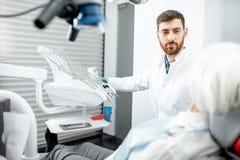 Dentista com o paciente superior da mulher no escritório dental imagens de stock