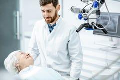 Dentista com o paciente superior da mulher no escritório dental da cirurgia imagens de stock royalty free