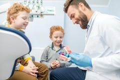 Dentista com os meninos no escritório dental foto de stock royalty free