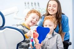 Dentista com os meninos no officee dental fotos de stock royalty free