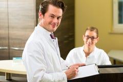 Dentista com a prancheta em sua cirurgia Fotografia de Stock
