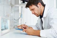 Dentista con l'immagine dei raggi x che prende le note Immagini Stock
