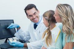 Dentista con la niña que muestra auxiliar su radiografía de la boca Imagen de archivo libre de regalías