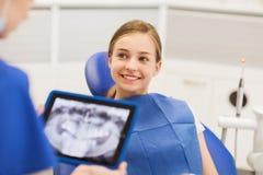 Dentista con la radiografía en la PC de la tableta y el paciente de la muchacha Fotos de archivo