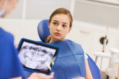Dentista con la radiografía en la PC de la tableta y el paciente de la muchacha Imagen de archivo libre de regalías