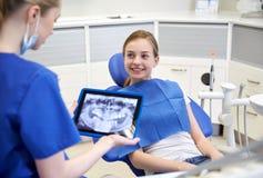 Dentista con la radiografía en la PC de la tableta y la muchacha del paciente Imagen de archivo libre de regalías