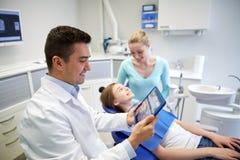 Dentista con la radiografía en la PC de la tableta y la muchacha del paciente Imagen de archivo
