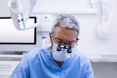 Dentista con le lenti di ingrandimento chirurgiche Fotografie Stock