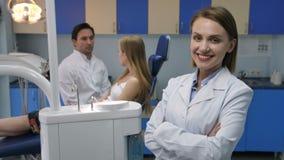 Dentista consideravelmente fêmea que sorri com os braços cruzados video estoque