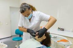 Dentista da fêmea adulta que trata os dentes pacientes da mulher Conceito da medicina, da odontologia e dos cuidados médicos imagem de stock