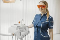 Dentista da mulher no uniforme azul que está ao lado do equipamento dental no stomatology fotografia de stock royalty free