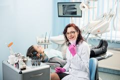 Dentista de la mujer con el paciente en la clínica dental Imagen de archivo libre de regalías