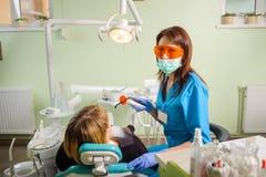Dentista de sexo femenino con la lámpara del photopolymer del dentista Fotos de archivo libres de regalías
