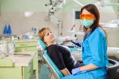 Dentista de sexo femenino con la lámpara del photopolymer del dentista Imágenes de archivo libres de regalías
