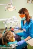Dentista de sexo femenino con la lámpara del photopolymer del dentista Fotos de archivo