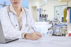 Dentista de sexo femenino con la prescripción en el lugar de trabajo Imágenes de archivo libres de regalías