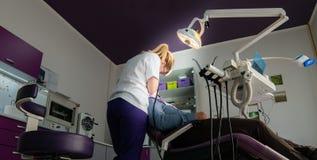 Dentista de sexo femenino con las herramientas dentales que comprueba encima de los dientes pacientes imagenes de archivo