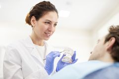 Dentista de sexo femenino Consulting Patient foto de archivo